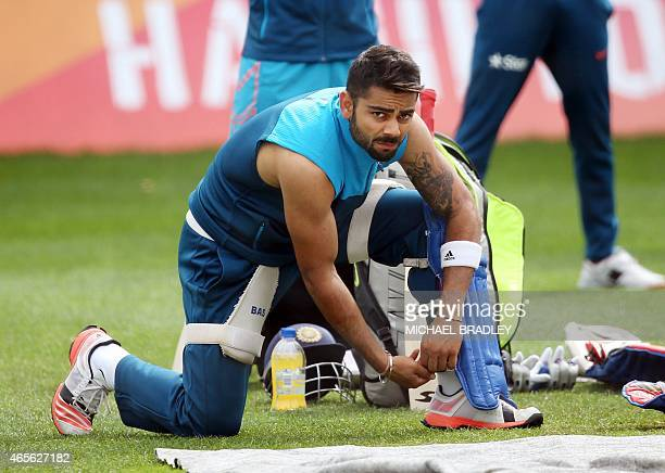India's Virat Kohli puts on his protective pads during a training session ahead of their 2015 Cricket World Cup Group B match against Ireland in...