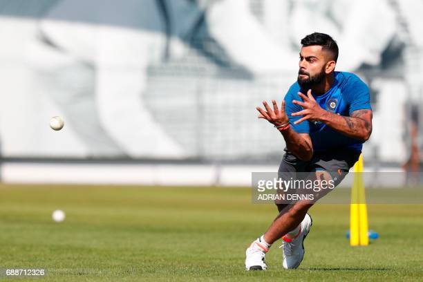 India's Virat Kohli takes a catch during a practice session at Lord's Cricket Ground in London on May 26 2017 ahead of the start of the 2017 2017 ICC...