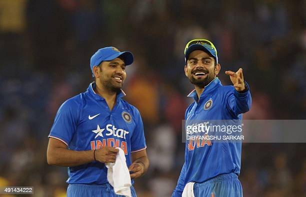 India's Virat Kohli talks with Rohit Sharma as play is interrupted by spectators throwing bottles onto the pitch during the second T20 cricket match...