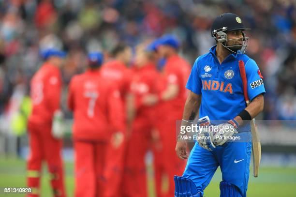 India's Virat Kohli walks off as England players celebrate during the ICC Champions Trophy Final at Edgbaston Birmingham