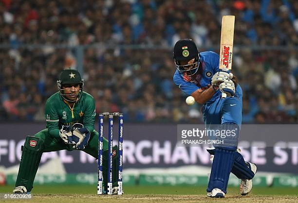 India's Virat Kohliplays a shot as Pakistan's Sarfaraz Ahmed looks on during the World T20 cricket tournament match between India and Pakistan at the...