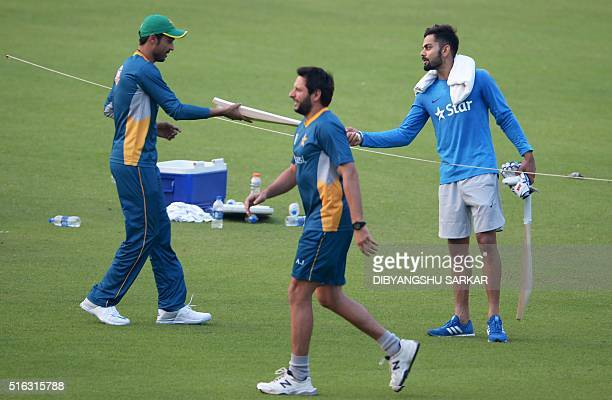 India's Virat Kohlipresents a cricket bat to Pakistan's Mohammad Amir as Pakistan's captain Shahid Afridi walks past during a training session at The...