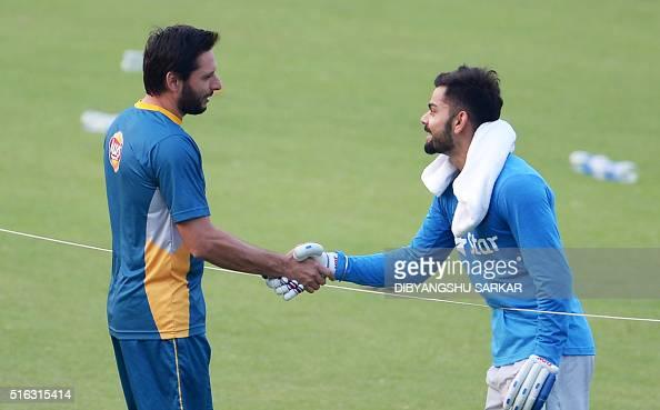 India's Virat Kohlishakes hands with Pakistan's captain Shahid Afridi during a training session at The Eden Gardens Cricket Stadium in Kolkata on...