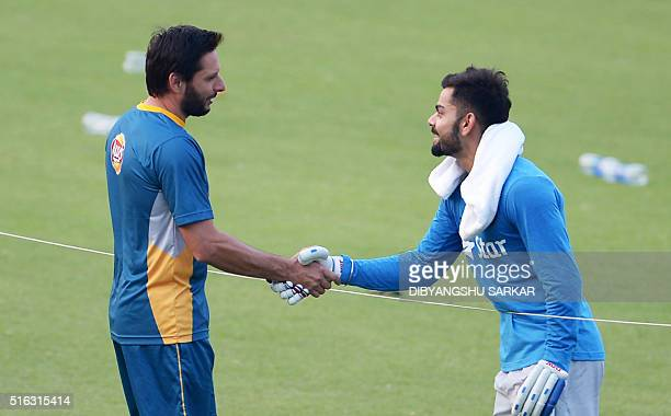 India's Virat Kohlishakes hands with Pakistan's captain Shahid Afridi during a training session at The Eden Gardens Cricket Stadium in Kolkata on...