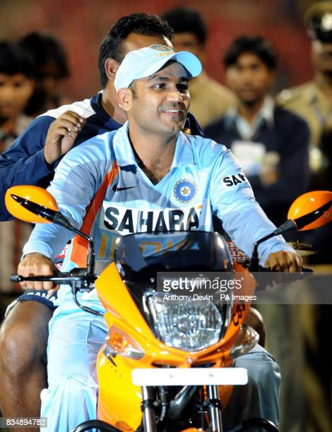 India's Virender Sehwag holds rides a motorbike following the Fourth One Day International at M Chinnaswamy Stadium Bangalore India