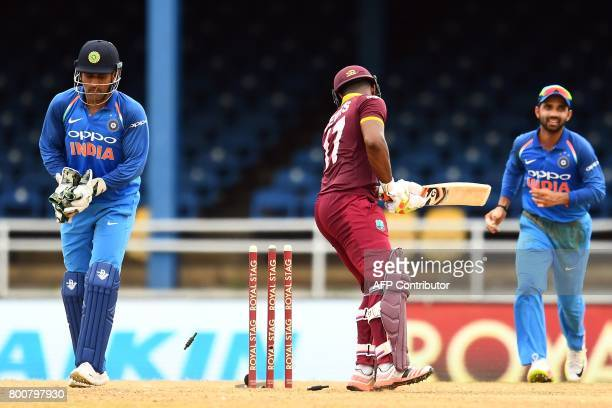 India's wicketkeeper MS Dhoni breaks the wicket to dismiss West Indies' Evin Lewis during the second One Day International match between West Indies...