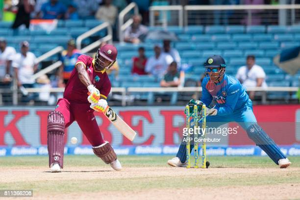 India's wicketkeeper MS Dhoni fields as West Indies' Evin Lewis plays a shot during the T20 match between West Indies and India at the Sabina Park...