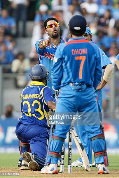 India's Yuvraj Singh discusses with captain and wicketkeeper Mahendra Singh Dhoni whether they should refer the LBW shout against Sri Lanka's Thilan...