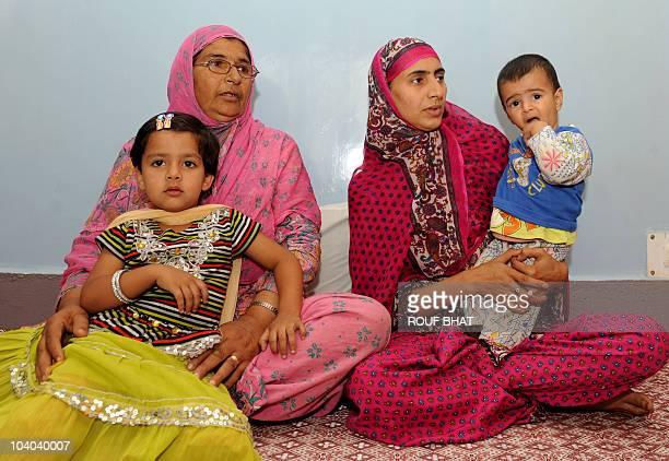 IndiaunrestKashmirEidFOCUS by Izhar Wani Kashmiri children Ayesha Fayaz and Mariyam Fayaz are held by their grandmother and mother at their residence...
