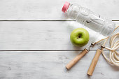 Green Apple, water bottle and jump rope on white wooden.close up.