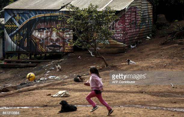 A indigenous child from a Guarani tribe plays with a ball in the Pico de Jaragua national reserve in Sao Paulo Brazil on August 31 2017 A group of...