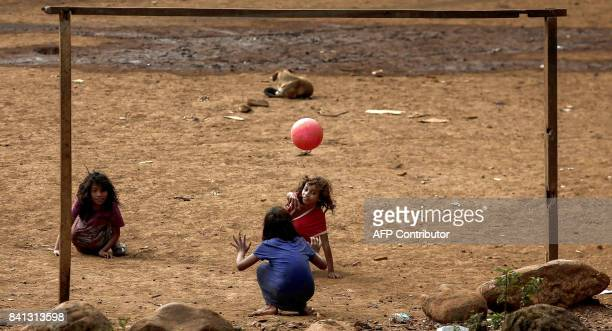 Indigenous children from a Guarani tribe play with a ball in the Pico de Jaragua national reserve in Sao Paulo Brazil on August 31 2017 A group of...