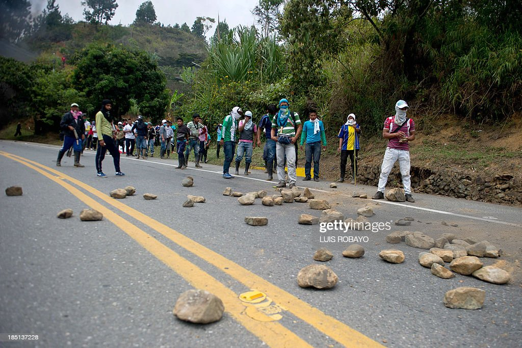 Indigenous Colombians face riot police during a protest on the Panamerican highway in Mondomo department of Cauca Colombia on October 17 2013...