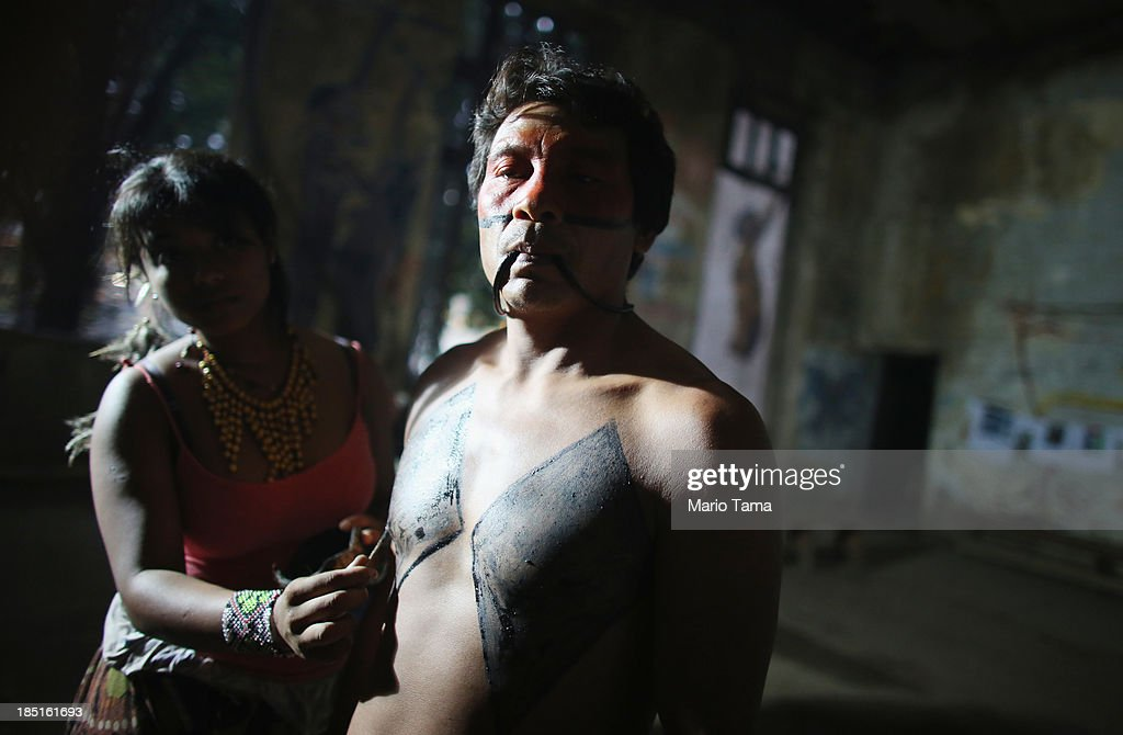 Indigenous community member Francisco (C) has traditional markings applied in the Aldeia Maracana building the group is occupying, next to Maracana Stadium, the site of the 2014 World Cup finals, on October 17, 2013 in Rio de Janeiro, Brazil. The fading Aldeia Maracana used to house the Museum of Indian Culture before deteriorating and becoming occupied by squatting indigenous members in 2006. The building was slated for destruction ahead of the 2014 World Cup and the community was forcibly evicted in March. However, the community has managed to return and thus far have successfully battled to save the structure, which they hope to convert into an indigenous university. Indigenous groups throughout Brazil are battling the Brazilian government over land rights and other issues.