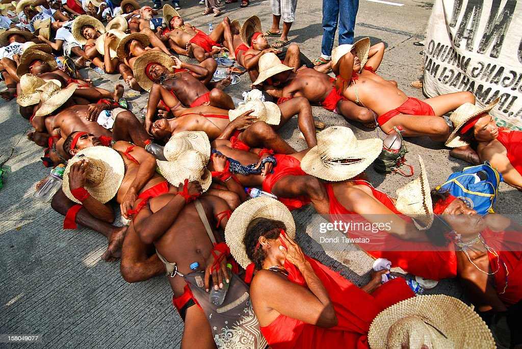 Indigenous farmers and fishermen stage a 'die-in' protest to dramatize their plight upon their arrival in Quezon City on December 10, 2012 in Manila, Philippines. An indigenous group of Dumagat tribes, farmers and fisherfolk are traveling 350 kilometers by foot from the northern region of Casiguran, Aurora to the capital city of Manila in an effort to stop the construction of an export processing zone called APECO, or the Aurora Pacific Ecozone and Freeport Authority. The farmers say the project has already displaced 3,000 families in the area and will remove their sources of livelihood and disrupt their lives. A total of 12,000 hectares of farm and coastal lands has been appropriated for the project.