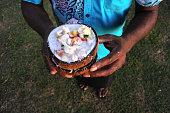 Indigenous Fijian Man serves Fijian Food, Kokoda (Raw Fish Salad). Kokoda is Fiji's version of ceviche, enriched with coconut milk to balance out all the acid.Real people, copy space