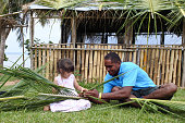 Indigenous Fijian man teach young tourist girl how to create a basket from weaving a Coconut Palm leaves.Travel Fiji concept, Real people copy space