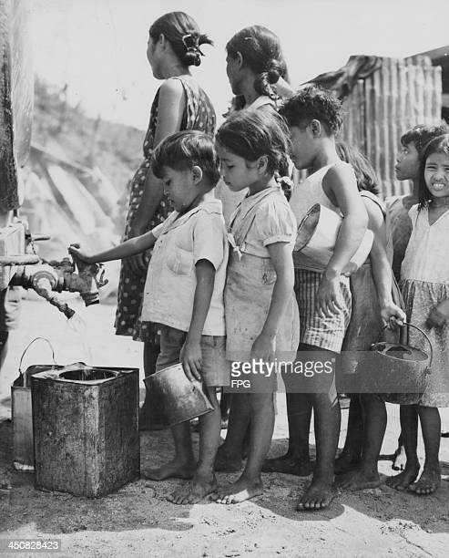 Indigenous Guam children waiting for fresh water supplies from US marines during the Pacific Campaign of World War Two Guam circa 19431945