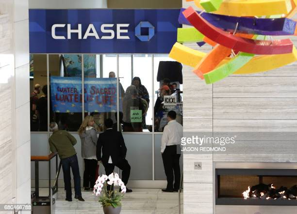 Indigenous leaders and climate activists disrupt business at a Chase Bank branch in Seattle on May 8 2017 Demonstrators protested bank funding for...