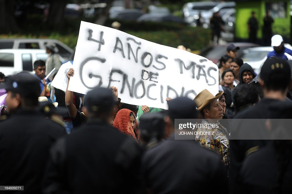 Indigenous men carrya banner reading 'Four more years of genocide' during a protest in Guatemala City on October 12 2012 The protest took place as a...
