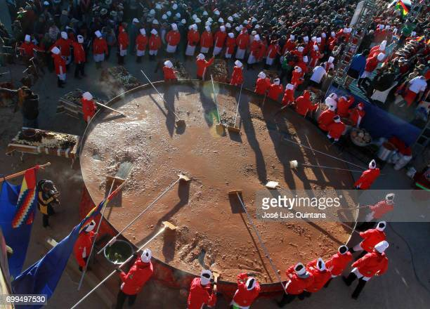 Indigenous people and local authorities stir a giant batch of traditional soup Kalapari during the celebration of the AndeanAmazonic New Year 5525 on...
