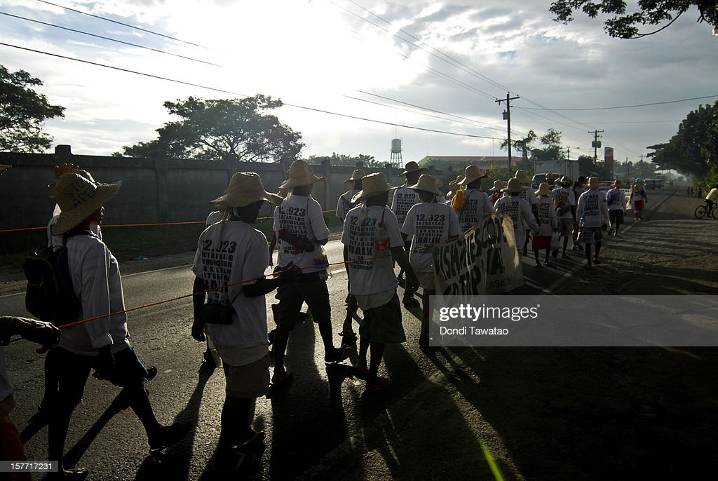 Indigenous people, farmers and fisherfolk walk at dawn in Cabanatuan on December 6, 2012 in Nueva Ecija, Philippines. An indigenous group of Dumagat tribes, farmers and fisherfolk are traveling 350 kilometers by foot from the northern region of Casiguran, Aurora to the capital city of Manila in an effort to stop the construction of an export processing zone called APECO, or the Aurora Pacific Ecozone and Freeport Authority. The farmers say the project has displaced 3,000 families in the area and will remove their sources of livelihood and disrupt their lives. A total of 12,000 hectares of farm and coastal lands has been appropriated for the project.