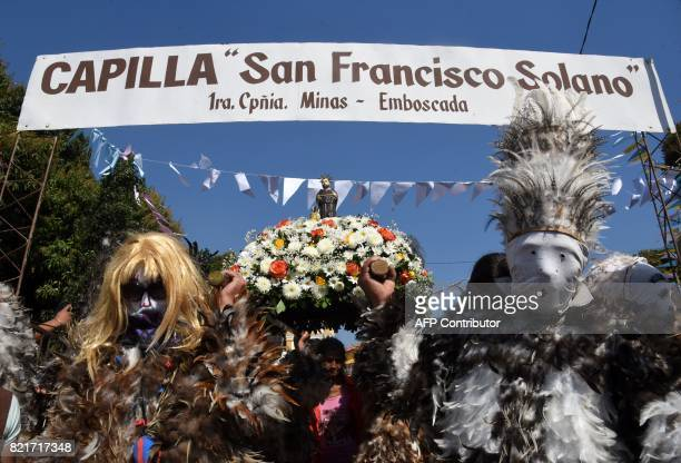 Indigenous people wearing masks and dressed in costumes made of hen feathers pay tribute to their patron saint San Francisco Solano and thank him for...