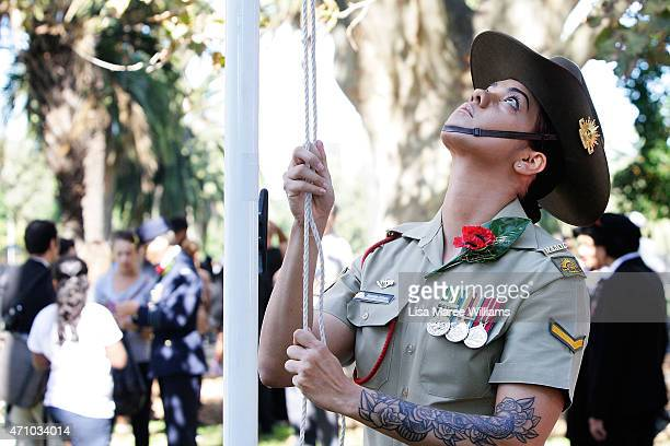Indigenous servicewoman Natalie Whyte of the Australian Armed Forces raises the Australian flag during the Redfern Aboriginal ANZAC Day Commemoration...