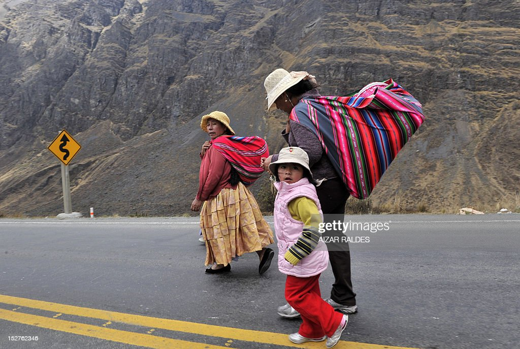 Indigenous women walk along a road linking La Paz with Las Yungas, near Pongo, 35 km northeast of La Paz, which was blocked by miners demanding the government the cession to their sector of the right of exploitation of the tin-rich Rosario seam, on September 25, 2012. AFP PHOTO/Aizar Raldes