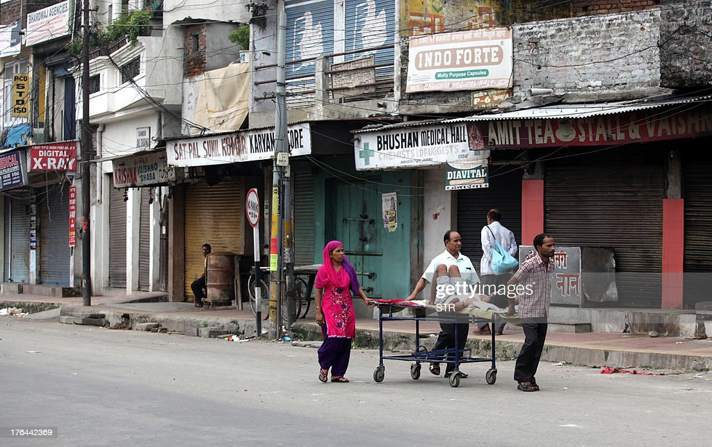 Indina medical attendants transport a patient on a stretcher along a deserted street during curfew in Jammu on August 13, 2013. The indefinite curfew was continued in Jammu in the wake of communal clashes in Kishtwar and the Centre has asked the Jammu and Kashmir Government to ensure peace by deploying adequate forces in all parts of the State.