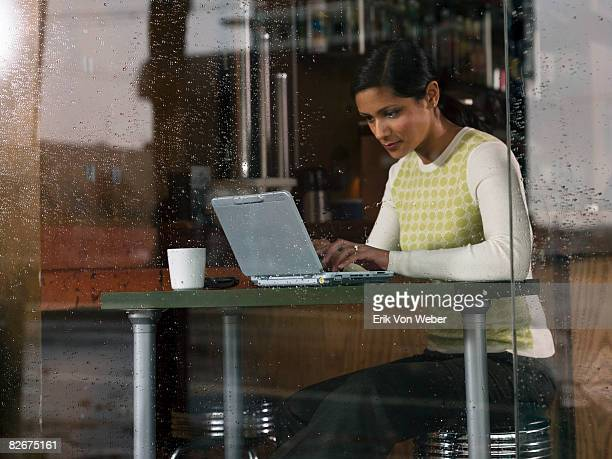 Individual with laptop in a cafe on a rainy day