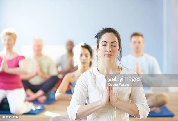 Individual woman at front of meditation group.