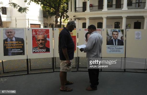 IndoFrench citizen interact with each other in front of a display of portraits of French presidential candidates on the premises of a polling booth...