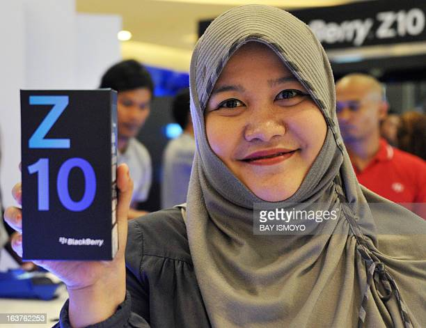 Indoneisan Diana Monasapti shows her new Blackberry Z10 she bought at its launching event at a shopping mall in Jakarta on March 15 2013 BlackBerry...