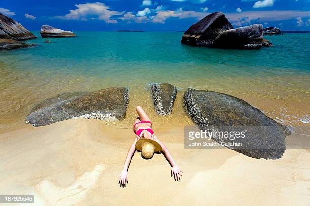 Indonesia, asian woman relaxing on beach.