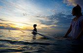 Indonesia, Bali, Canggu, two female surfer in the water watching sun