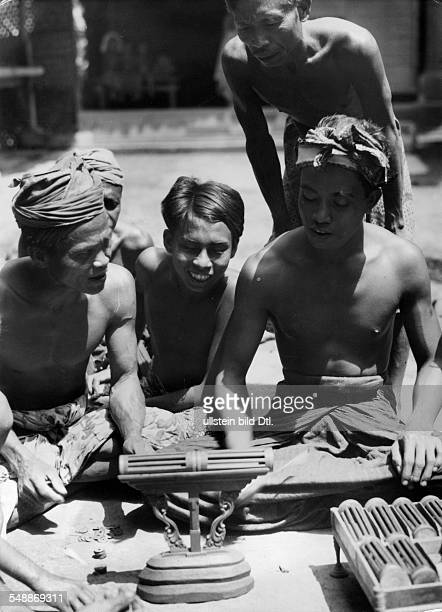 Indonesia Bali Denpasar A group of boys sitting infront of small bamboo cages with crickets inside um 1938 Photographer Hugo Adolf Bernatzik Vintage...