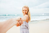 Indonesia, Bali, smiling woman on beach pulling hand of a man