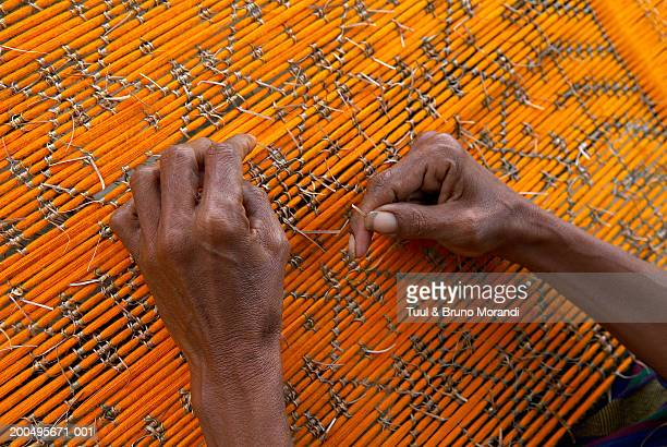 Indonesia, Flores, Ende, Wolotopo village, man weaving Ikat