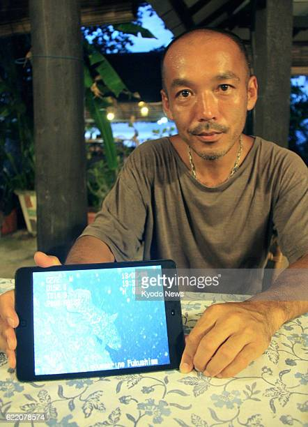MANADO Indonesia Masamitsu Iwata a researcher at Aquamarine Fukushima shows an image of a coelacanth taken by an expedition team he leads off Manado...