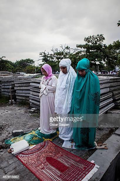 Indonesia Muslims pray after Eid ElFitr pray at Sunda Kelapa Port on July 28 2014 in Jakarta Indonesia Eid AlFitr marks the end of Ramadan the...