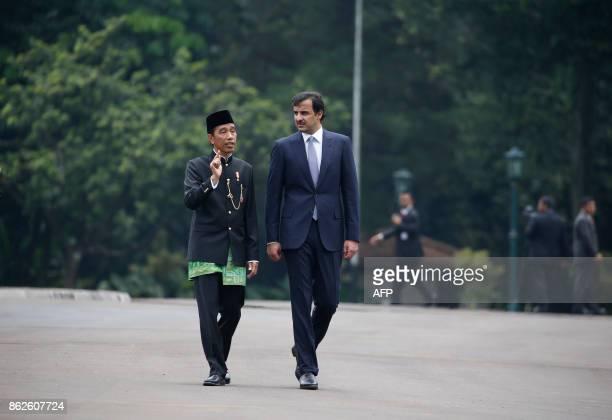 Indonesia President Joko Widodo talks to Qatar's Emir Sheikh Tamim bin Hamad alThani as they walk for a tree planting ceremony at the presidential...