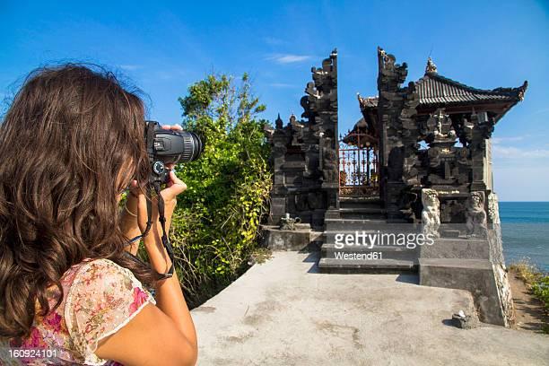 Indonesia, Tourist taking photograph of Batu Bolong Temple