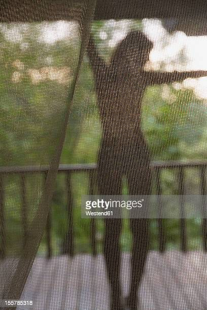 Indonesia, Young woman standing behind net on wooden veranda