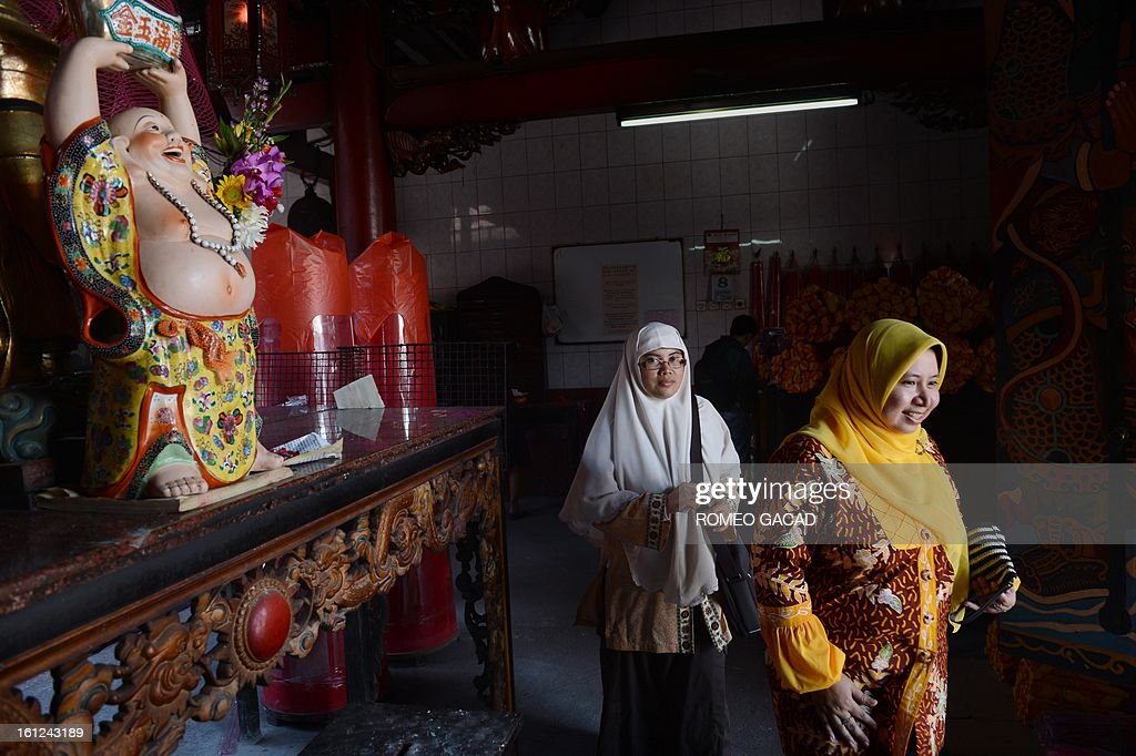'Indonesia-China-religion-Islam,FEATURE' BY KEVIN PONNIAH In this photograph taken on February 8, 2013, Muslim women Widi Astuti (L) and Lusi Kusuma (R) visit a Buddhist temple in the Indonesian capital city of Jakarta as minority Chinese-Indonesians celebrate the Chinese Lunar New Year. As Indonesia and other countries with Chinese diasporas welcome the Year of the Snake, hardline Islamic leaders have ignited a religious row by declaring the celebrations 'haram' and off limits for Muslims. AFP PHOTO / ROMEO GACAD