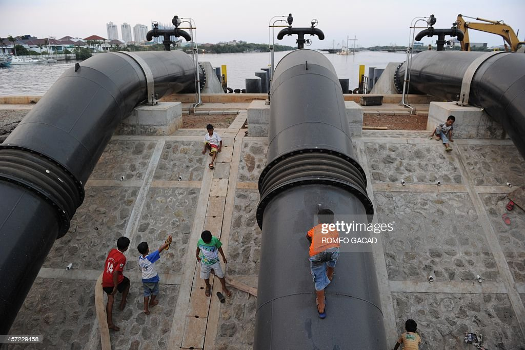 Indonesia-flood-environment-construction FOCUS, by Sam Reeves In this photograph taken October 9, 2014, children residing in the slum area play on giant pipes of a flood control station built along a dike protecting the community from sea water intrusions as construction of the Jakarta sea wall begins in the northern coastal district of Jakarta. The Indonesian capital Jakarta has launched an ambitious, multi-billion-dollar plan to build an enormous sea wall to combat the increased threat of flooding as the sprawling metropolis rapidly sinks. The whole project costing up to 40 billion USD over many years, and also includes reclaiming land for a series of islands will form the shape of a Garuda, the mythical bird that is Indonesia's national symbol.