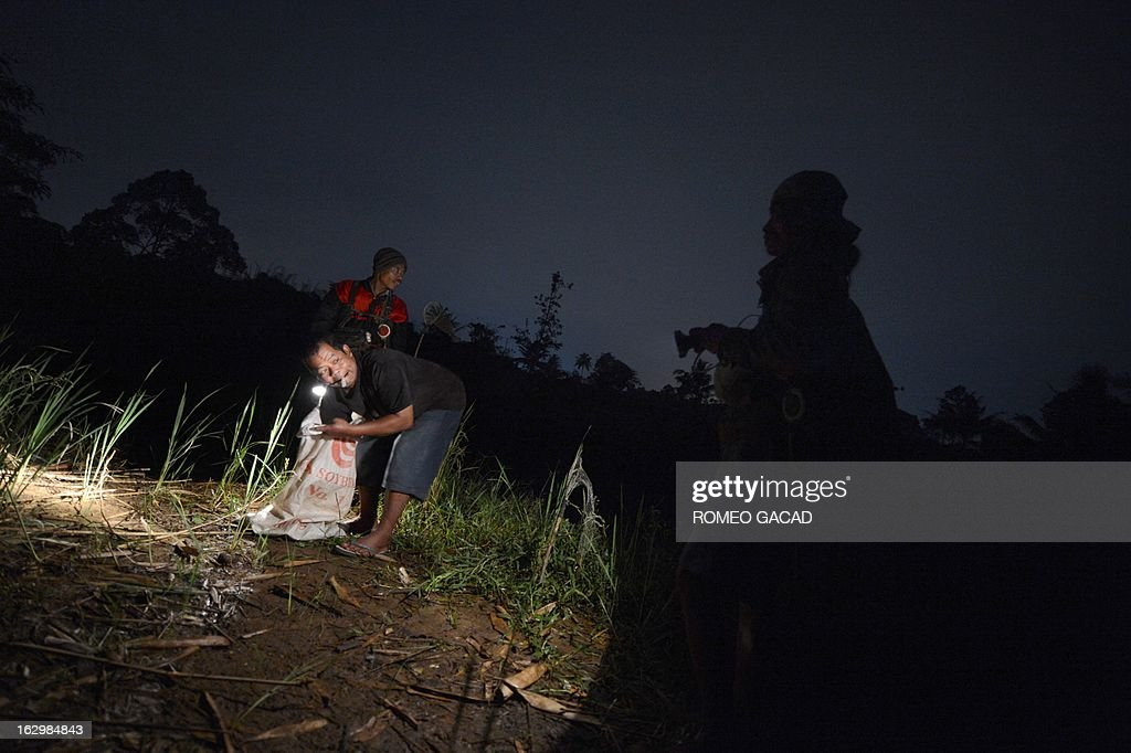 Indonesia-France-environment-food-species-frogs,FEATURE by Kevin PONNIAH In this photograph taken on February 11, 2013, three Indonesian frog hunters Suwanto (L-with sack), Padang (L-at back) and Emul (R) search rice fields in the village of Cimande near Bogor, located in the western outskirts of Jakarta, to supply local tastes and the highly lucrative foreign demand for frogs. Indonesia has become the world's biggest exporter of frogs, providing more than 80 percent of Europe's imports, almost all caught in the wild by village-style frog hunters like Suwanto.