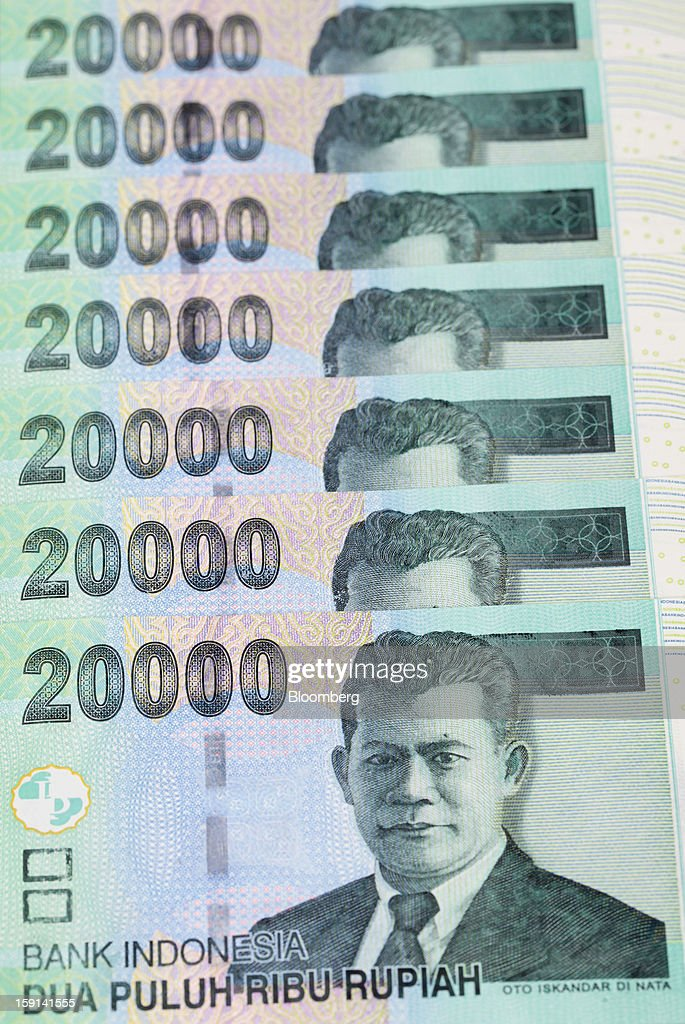Indonesian 20,000 rupiah banknotes are arranged for a photograph in Jakarta, Indonesia, on Tuesday, Jan. 8, 2013. Indonesia's rupiah weakened by the most in six months on concern the government's failure to meet its spending target last year will hamper economic growth and damp demand for local assets. Photographer: Dimas Ardian/Bloomberg via Getty Images
