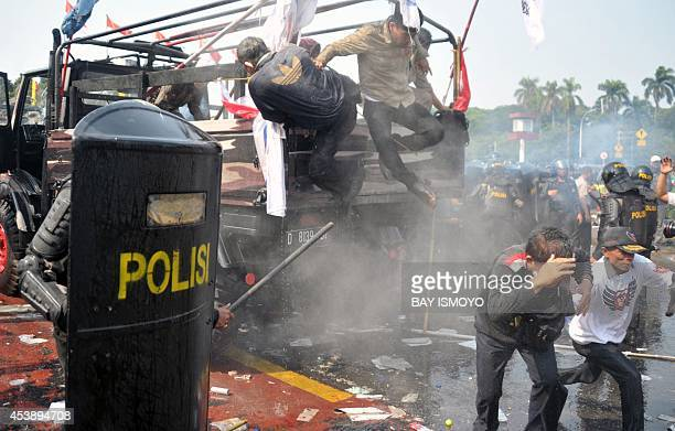 Indonesian antiriot police move in to arrest supporters of presidential candidate Prabowo as they try to pass a blockade near the constitutional...