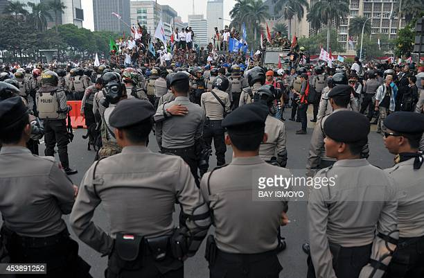 Indonesian antiriot police stand guard as presidential candidate Prabowo's supporters try to pass a blockade near the constitutional court in Jakarta...